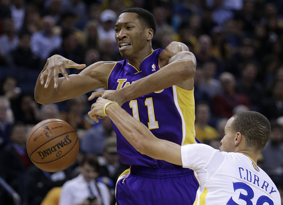 Photo - Los Angeles Lakers' Wesley Johnson, left, loses control of the ball against Golden State Warriors' Stephen Curry during the first half of an NBA basketball game Saturday, Dec. 21, 2013, in Oakland, Calif. (AP Photo/Ben Margot)