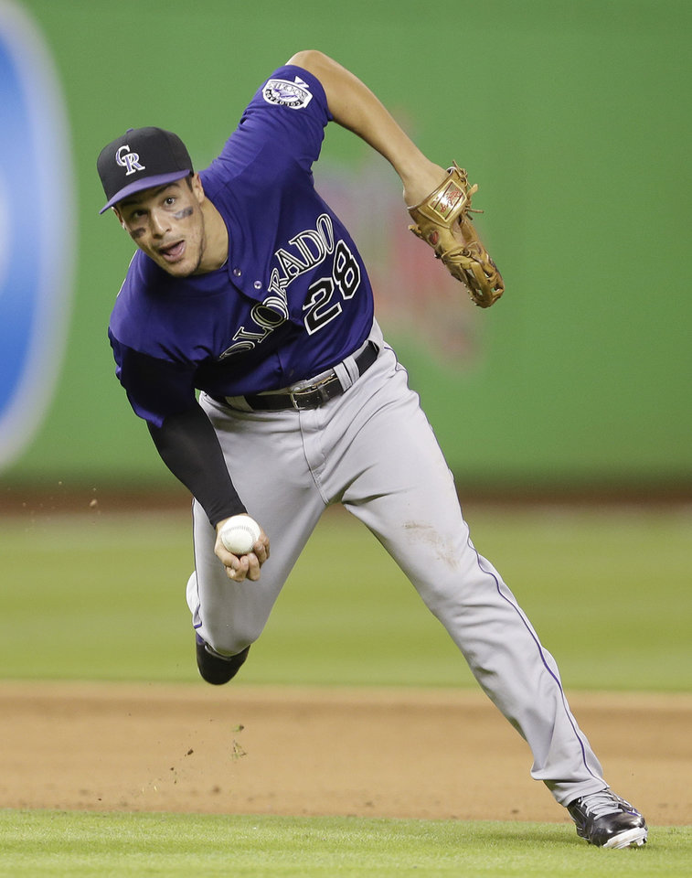 Photo - Colorado Rockies third baseman Nolan Arenado throws  late to first base in the fifth inning during the inning of an opening day baseball game, Monday, March 31, 2014, in Miami. (AP Photo/Lynne Sladky)