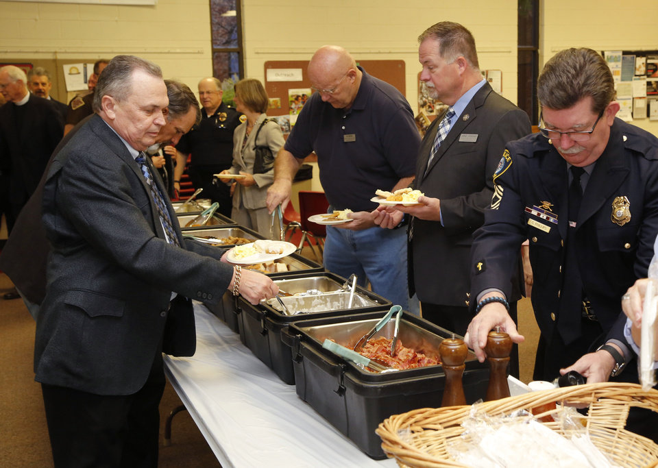Photo -  Oklahoma County Sheriff John Whetsel, left, joins law enforcement officers and Edmond residents for a prayer breakfast. [PHOTO BY PAUL HELLSTERN, THE OKLAHOMAN]