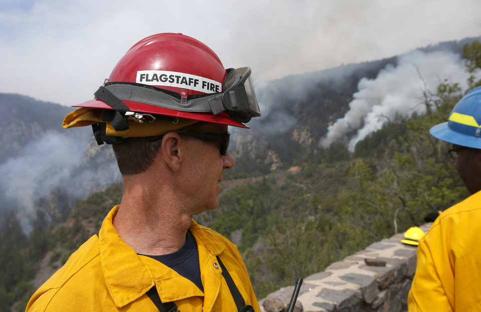 Photo - Bill Morse, the public information officer for the Southwest Area Type 1 Incident Management Team, watches the Slide Fire as it burns up Oak Creek Canyon on Friday, May 23, 2014, near Flagstaff, Ariz.  The fire has burned approximately 7,500 acres and is five percent contained. (AP Photo/Ross D. Franklin)