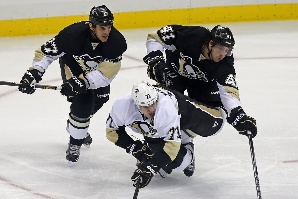 Pittsburgh Penguins' White Team's Evgeni Malkin (71) collides with Penguin's Black Team's Craig Adams (27) and Robert Bortuzzo (41) during the first period of an NHL hockey scrimmage in Pittsburgh, Wednesday, Jan. 16, 2013. (AP Photo/Gene J. Puskar)