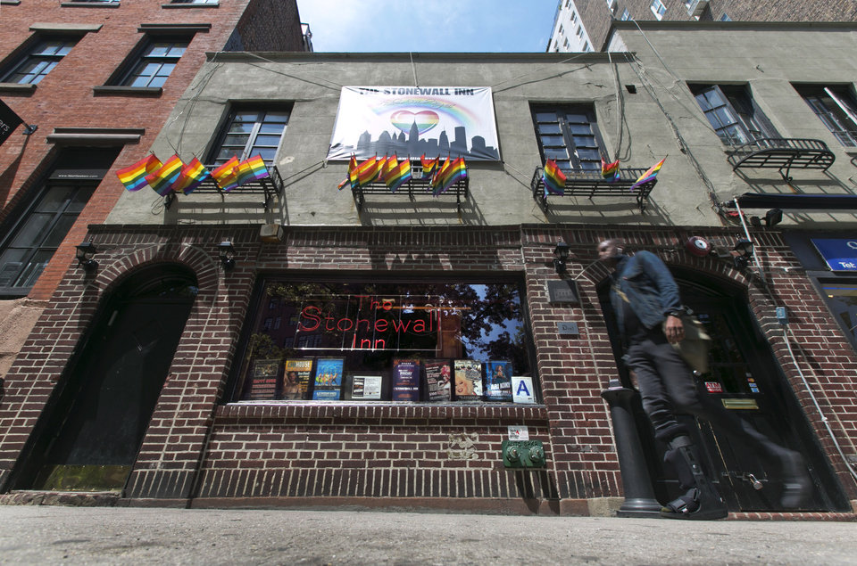 Photo - A man passes The Stonewall Inn, in New York's Greenwich Village, Thursday, May 29, 2014. The National Park Service is launching an initiative to make places and people of significance to the history of lesbian, gay, transgender and bisexual Americans part of the national narrative. Interior Secretary Sally Jewell plans to announce the initiative on Friday at New York's Stonewall Inn, which was made a national historic landmark in 2000.(AP Photo/Richard Drew)