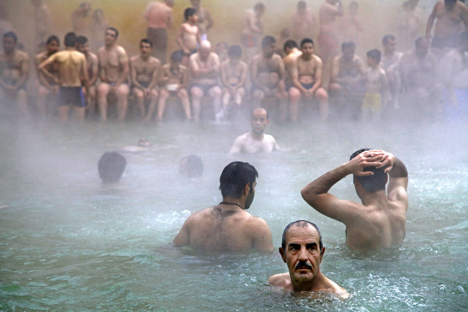 Photo - In this Sept. 11, 2013 photo, Iranian men enjoy a hot mineral water pool, in the northwestern town of Sarein, Iran. The steamy waters emanating from the depths of the earth are rich in sulfur, calcium, lithium and other minerals, and are believed to offer relief to patients suffering from joint pain and some skin diseases. (AP Photo/Ebrahim Noroozi)