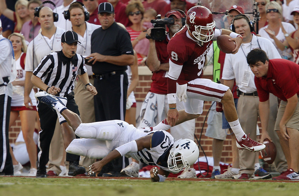 Oklahoma's Trevor Knight (9) leaps over West Virginia's Darwin Cook (25) during a college football game between the University of Oklahoma Sooners (OU) and the West Virginia University Mountaineers at Gaylord Family-Oklahoma Memorial Stadium in Norman, Okla., on Saturday, Sept. 7, 2013. Photo by Bryan Terry, The Oklahoman