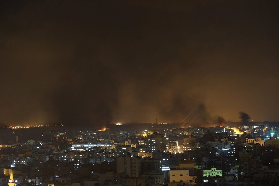 Photo - In this image made with a slow exposure, smoke from Israeli strikes rises in the sky over Gaza City, northern Gaza Strip, late Saturday, July 19, 2014. Gaza Health Ministry spokesman Ashraf al-Kidra said the new round of strikes raised the death toll from the 12-day offensive to more than 330 Palestinians, many of them civilians and nearly a fourth of them under the age of 18.(AP Photo/Lefteris Pitarakis)