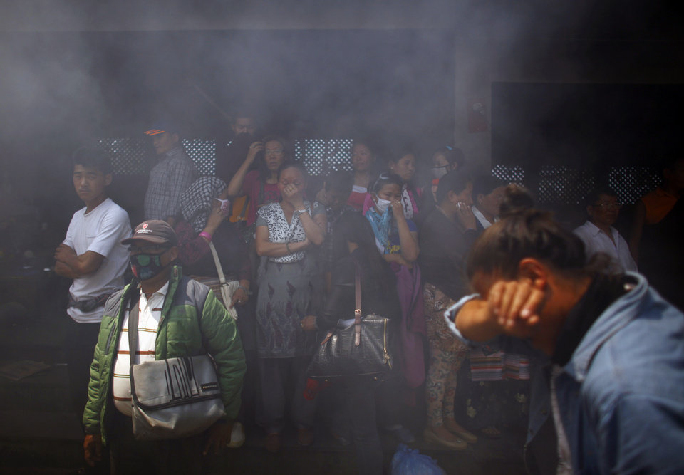 Photo - Smoke rises from the cremation pyre of mountaineers, killed in an avalanche on Mount Everest, during a funeral ceremony in Katmandu, Nepal, Monday, April 21, 2014. Buddhist monks cremated the remains of Sherpa guides who were buried in the deadliest avalanche ever recorded on Mount Everest, a disaster that has prompted calls for a climbing boycott by Nepal's ethnic Sherpa community. The avalanche killed at least 13 Sherpas. Three other Sherpas remain missing and are presumed dead. (AP Photo/Niranjan Shrestha)