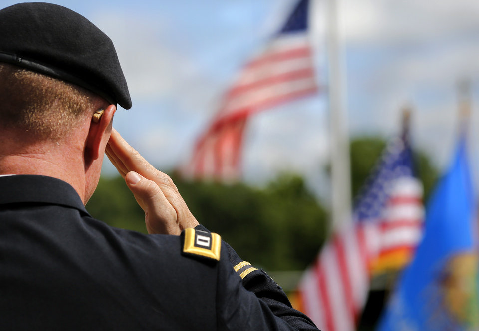 Photo -  Capt. Josh Byrd, chaplain with the 45th Infantry Brigade, salutes the American flag flying at half-staff as the colors are retired at the end of the program during the 45th Infantry Division Museum's Memorial Day Ceremony on Monday, May 30, 2016. Byrd delivered the invocation and the benediction. Photo by Jim Beckel, The Oklahoman