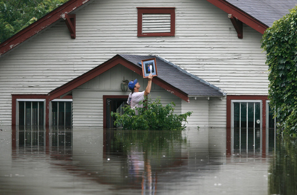 Photo - FLOOD, FLOODING, RAIN: Tony Freez retrieves a framed photograph from his boss' house in Miami, Okla., Tuesday, July 3, 2007. Floodwaters pushed into homes and businesses Tuesday as the rain-swollen Neosho River spilled over its banks, forcing hundreds of residents to evacuate, blocking access to key roads and sending water into classroom buildings and apartments at a state college. (AP Photo/Tulsa World, Stephen Holman) ORG XMIT: OKTUL105