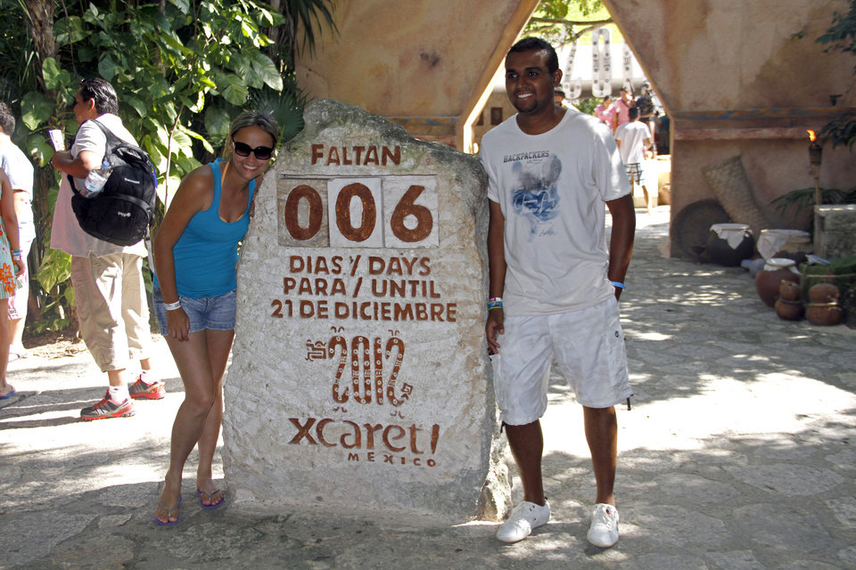 Tourists get their picture taken next to a slab of stone counting down the days until Dec. 21, 2012 at the Xcaret theme park in Playa del Carmen, Mexico, Saturday, Dec. 15, 2012. Amid a worldwide frenzy of advertisers and new-agers preparing for a Maya apocalypse, one group is approaching Dec. 21 with calm and equanimity calm: the people whose ancestors supposedly made the prediction in the first place. Mexico\'s 800,000 Mayas are not the sinister, secretive, apocalypse-obsessed race they\'ve been made out to be. (AP Photo/Israel Leal)
