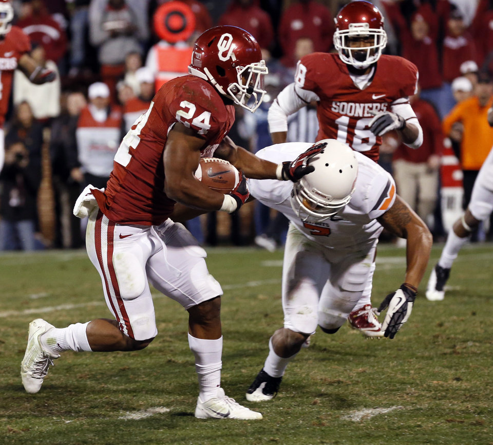 Oklahoma\'s Brennan Clay (24) pushes aside Oklahoma State\'s Shamiel Gary (7) and scores the game winning touchdown of the Bedlam college football game in which the University of Oklahoma Sooners (OU) defeated the Oklahoma State University Cowboys (OSU) 51-48 in overtime at Gaylord Family-Oklahoma Memorial Stadium in Norman, Okla., Saturday, Nov. 24, 2012. Photo by Steve Sisney, The Oklahoman