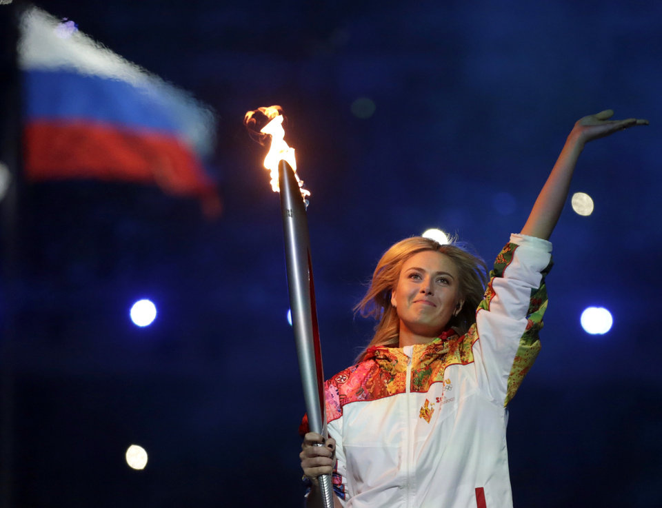 Photo - Russia's Maria Sharapova carries the torch during the opening ceremony of the 2014 Winter Olympics in Sochi, Russia, Friday, Feb. 7, 2014. (AP Photo/Matt Dunham)