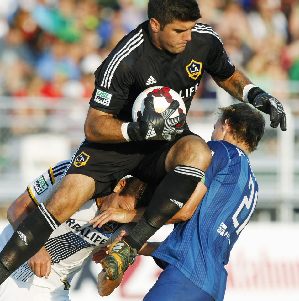 Photo - LA Galaxy II goalkeeper Cody Laurendi (41) jumps into the air and catches the ball while nearly elbowing Energy FC forward Steven Perry (21) during a USL Pro soccer game between OKC Energy FC and LA Galaxy II at Pribil Stadium in Oklahoma City on July 19, 2014. Photo by KT King,The Oklahoman