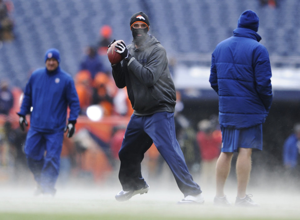 Photo - Denver Broncos quarterback Brock Osweiler warms up in seven degree Fahrenheit temperatures before playing the Baltimore Ravens in an AFC divisional playoff NFL football game, Saturday, Jan. 12, 2013, in Denver.  (AP Photo/Jack Dempsey)