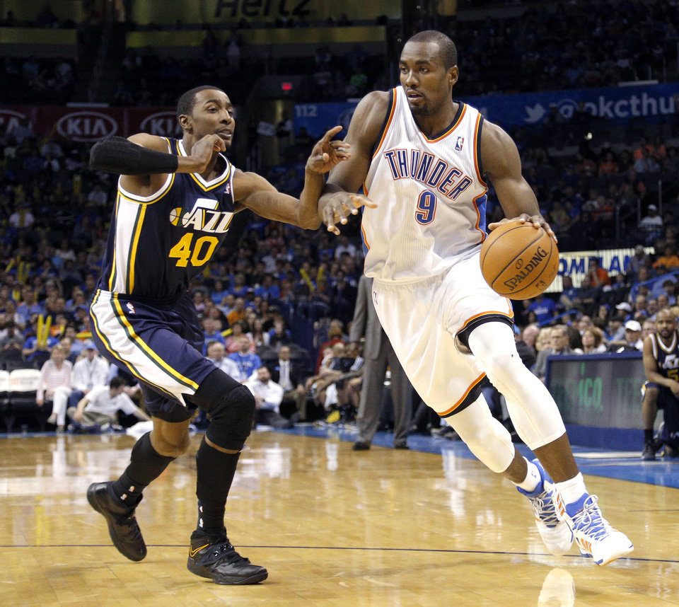 Photo - Oklahoma City 's Serge Ibaka (9) drives past Utah's Jeremy Evans (40) during the NBA game between the Oklahoma City Thunder and the Utah Jazz at the Chesapeake Energy Arena, Sunday, March 30, 2014, in Oklahoma City. Photo by Sarah Phipps, The Oklahoman