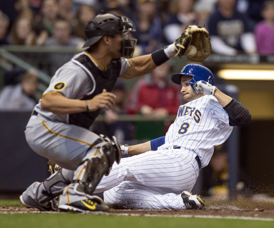 Photo - Milwaukee Brewers' Ryan Braun, right, slides ahead of the tag by Pittsburgh Pirates' Tony Sanchez during the fourth inning of a baseball game on Sunday, April 13, 2014, in Milwaukee. (AP Photo/Tom Lynn)