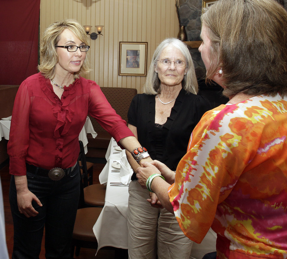 Photo - In this photo taken Friday, July 5, 2013, former Arizona Rep. Gabrielle Giffords greets Jackie Barden, right, mother of a Sandy Hook Elementary School shooting victim Daniel Barden, as local supporter Mary Ann Sosnoff, center, looks on at the Orchard Street Chop Shop in Dover, N.H.  Three years after being shot in the head, Giffords is in New Hampshire to urge support for background checks on gun purchases. (AP Photo/Mary Schwalm)