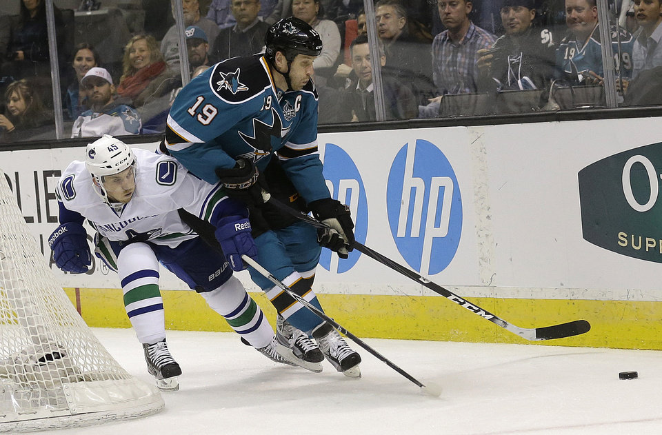 San Jose Sharks center Joe Thornton (19) tries to control the puck as Vancouver Canucks center Jordan Schroeder (45) defends during the first period of an NHL hockey game in San Jose, Calif., Monday, April 1, 2013. (AP Photo/Jeff Chiu)