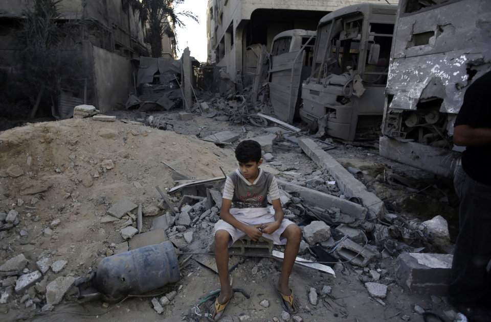 Photo - A Palestinian boy sits on rubble and next to destroyed buses and houses, following late night Israeli strikes in Gaza City, Wednesday, Aug. 20, 2014. (AP Photo/Khalil Hamra)