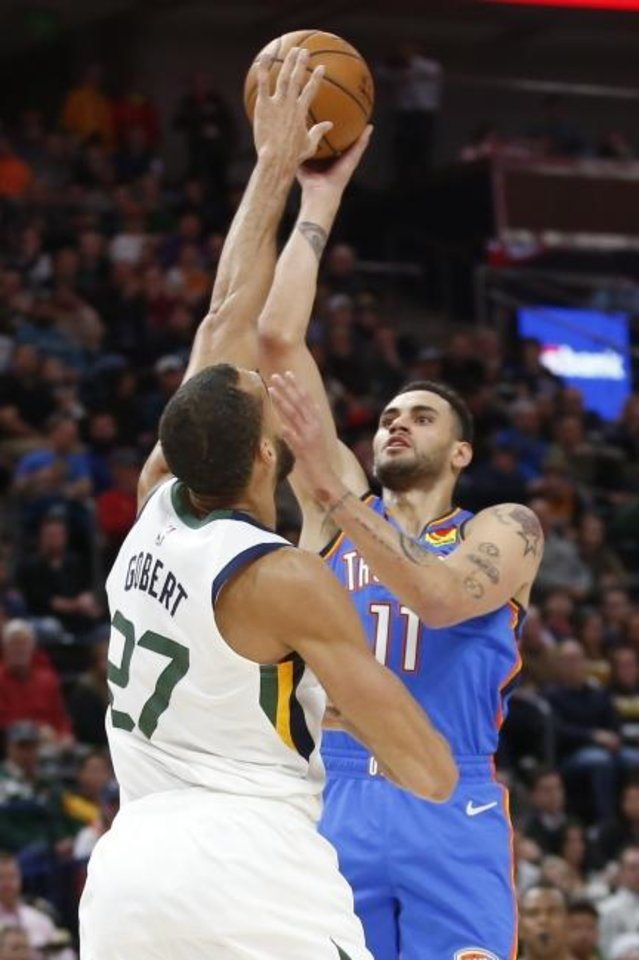Photo -  Oklahoma City Thunder forward Abdel Nader, right, shoots as Utah Jazz center Rudy Gobert defends in the first half of Monday's game in Salt Lake City. [AP Photo/Rick Bowmer]
