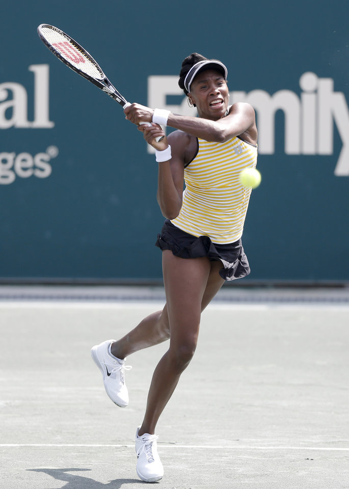 Photo - Venus Williams returns to Eugenie Bouchard, of Canada, during the Family Circle Cup tennis tournament in Charleston, S.C., Thursday, April 3, 2014. (AP Photo/Mic Smith)