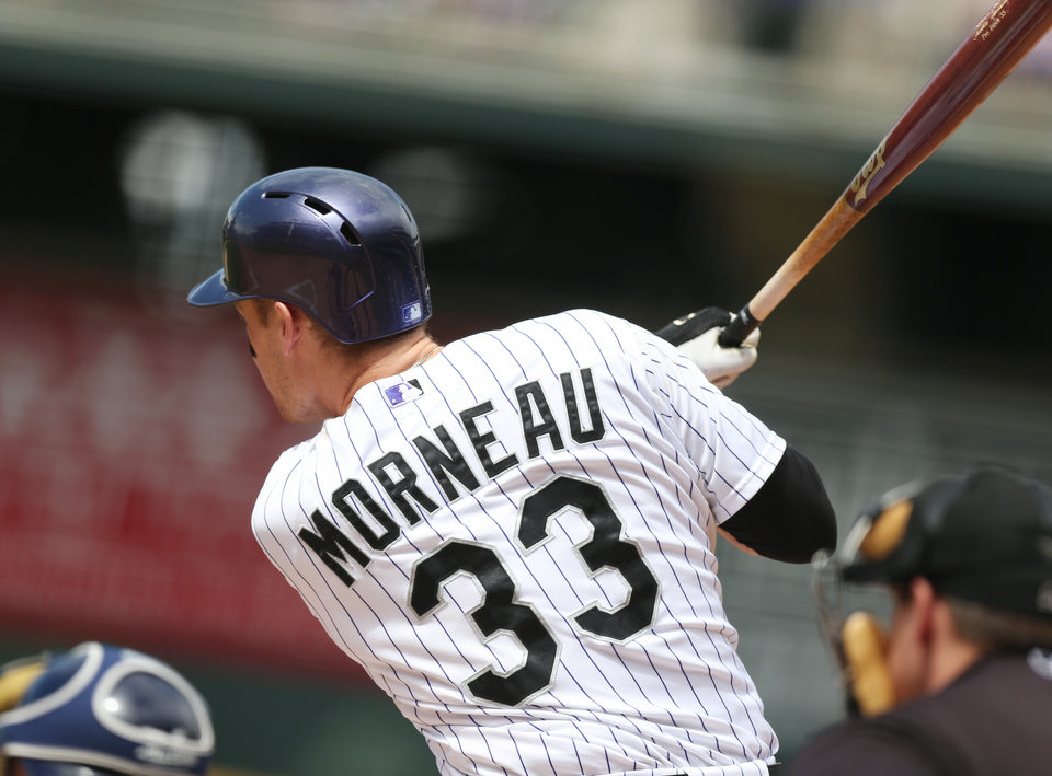 Photo - Colorado Rockies' Justin Morneau follows the flight of his two-run single against the Milwaukee Brewers in the first inning of a baseball game in Denver on Saturday, June 21, 2014. (AP Photo/David Zalubowski)