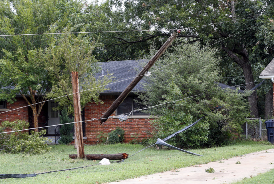 Photo - Downed power lines cross a yard on Virginia Ave. near NW 46 St. after thunderstorms went through the metro area, in Oklahoma City, Tuesday, Aug. 27, 2019. [Nate Billings/The Oklahoman]