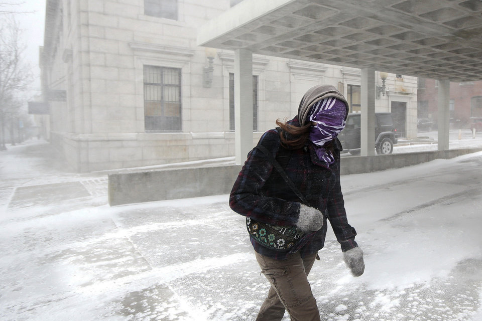 Photo - A woman fights through wind-driven snow as she crosses a street during a spring snowstorm in downtown New Bedford, Mass., Wednesday, March 26, 2014. The storm brought high winds that whipped snow across portions of Massachusetts and eastern Maine, causing near-whiteout conditions on Cape Cod and roiling the Atlantic as it moved up the coast.  (AP Photo/The Standard-Times, Peter Pereira)