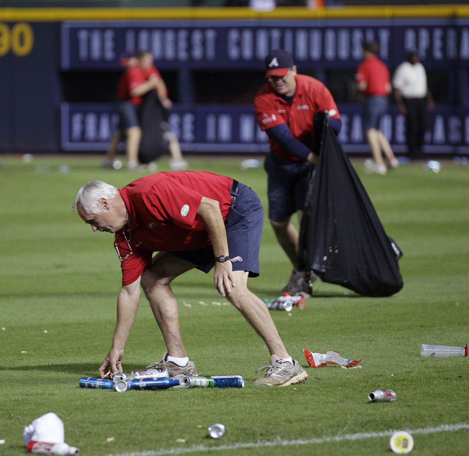 An Atlanta Braves official picks up trash on the field during the eighth inning of the National League wild card playoff baseball game against the St. Louis Cardinals, Friday, Oct. 5, 2012, in Atlanta. The Cardinals won baseball\'s first wild-card playoff, taking advantage of a disputed infield fly call that led to a protest and fans littering the field with debris to defeat the Braves 6-3. (AP Photo/John Bazemore)