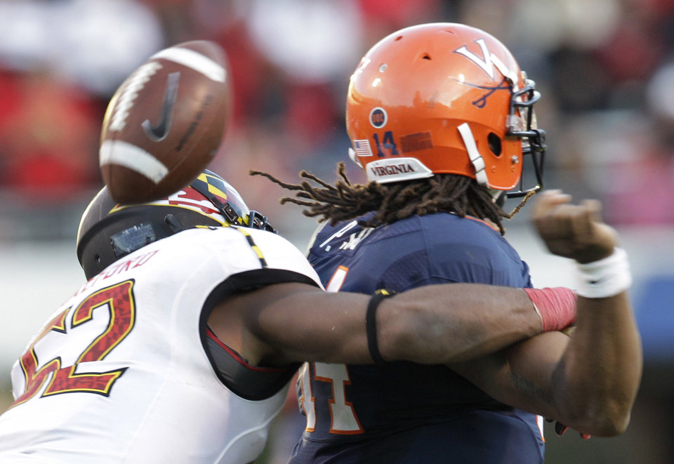 Photo -   Maryland linebacker Darin Drakeford (52) forces a fumble by Virginia quarterback Phillip Sims during the second half of an NCAA college football game in Charlottesville, Va., Saturday, Oct. 13, 2012. Maryland won 27-20. (AP Photo/Steve Helber)