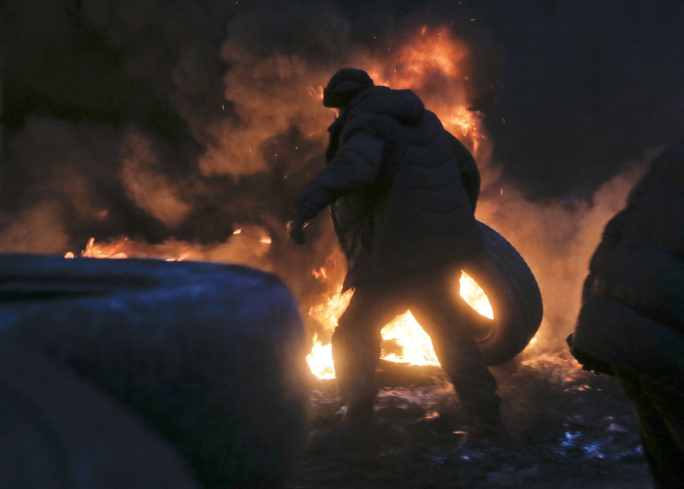Photo - An activist carries a tyre at the burning barricades close to Independence Square, the epicenter of the country's current unrest, in Kiev, Ukraine, Thursday, Feb. 20, 2014. Fierce clashes between police and protesters in Ukraine's capital have shattered the brief truce Thursday and an Associated Press reporter has seen dozens bodies laid out on the edge of the protest encampment.  (AP Photo/Efrem Lukatsky)