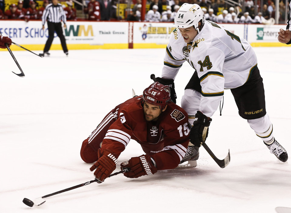 Photo - Phoenix Coyotes' Boyd Gordon (15) tries to get control of the puck as he is shoved by Dallas Stars' Jamie Benn (14) during the first period in an NHL hockey game Saturday, Feb. 2, 2013, in Glendale, Ariz. (AP Photo/Ross D. Franklin)