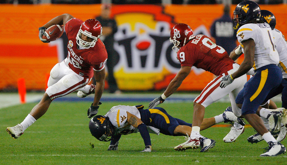 Photo - Oklahoma's Jermaine Gresham (18) is tripped up by West Virginia's Vaughn Rivers (19) during the first half of the Fiesta Bowl college football game between the University of Oklahoma Sooners (OU) and the West Virginia University Mountaineers (WVU) at The University of Phoenix Stadium on Wednesday, Jan. 2, 2008, in Glendale, Ariz. 