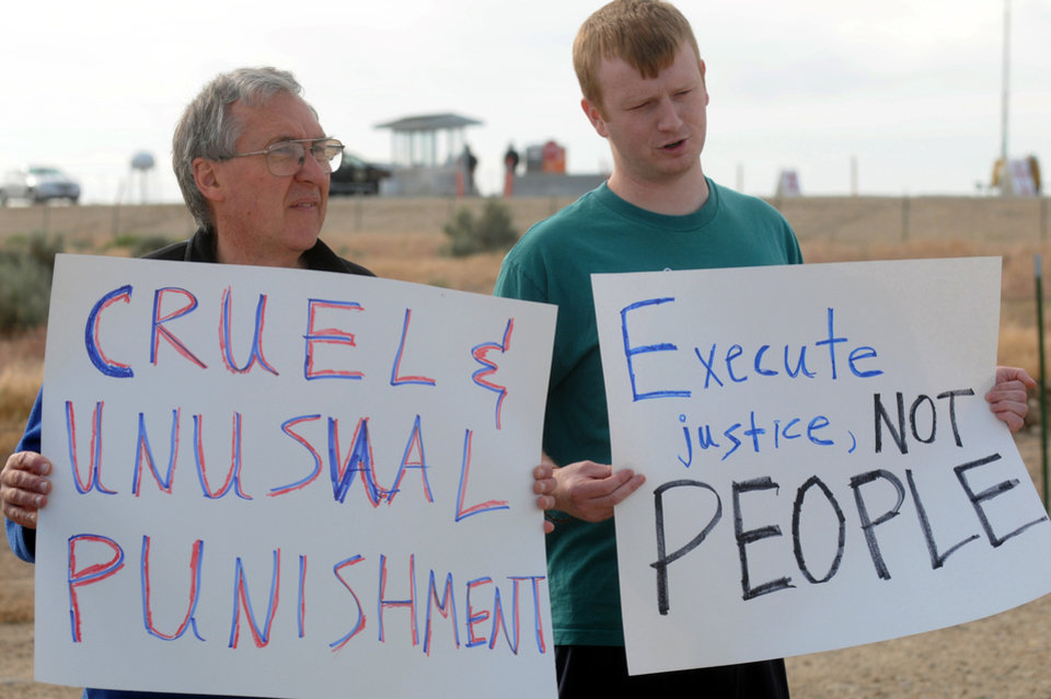 Photo - Chuck Skoro, left, and Greg Franz, both of Boise, Idaho, join a small group of protesters outside the Idaho Department of Corrections in opposition to the scheduled execution of Richard Leavitt on Tuesday, June 12, 2012 in Kuna.  Prison officials declared Leavitt, 53,  dead at 10:25 a.m. Tuesday by lethal injection at the Idaho Maximum Security Institution. It was only Idaho's second execution in 17 years.  Leavitt was convicted of stabbing 31-year-old Danette Elg, of Blackfoot, in 1984. Leavitt's execution marked the first time witnesses had full viewing access to a convicted killer's lethal injection after the 9th U.S. Circuit Court of Appeals a few days before the execution sided with The Associated Press and other news organizations seeking full viewing access to a convicted killer's lethal injection.  (AP Photo/Idaho Press-Tribune, Greg Kreller) MANDATORY CREDIT