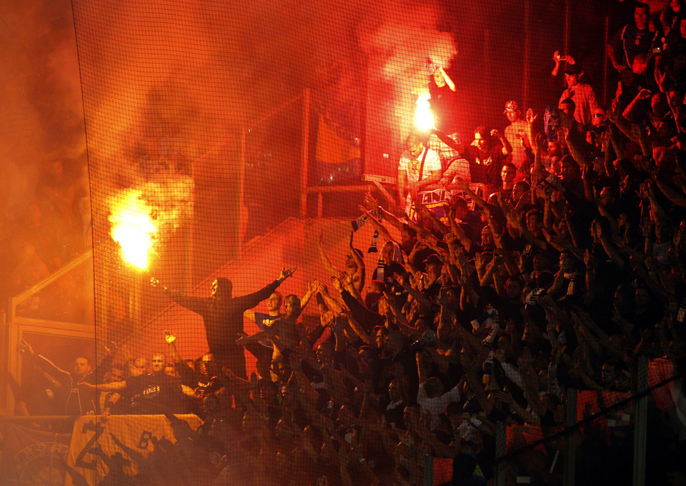 Bosnia-Herzegovina fans burn flares during a World Cup Group G qualifying soccer match between Greece and Bosnia-Herzegovina, at Karaiskaki stadium, in Piraeus port, near Athens, Friday, Oct. 12, 2012. (AP Photo/Petros Giannakouris)