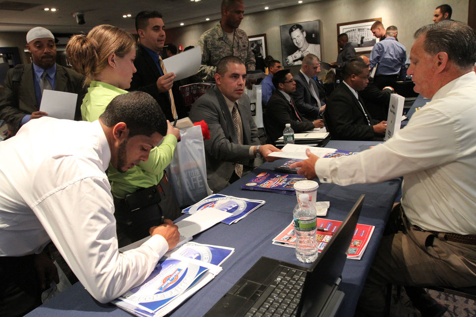 Veteran Luis Gomez, 40, from Dover, N.J., seated center, hands his resume to a representative from White Rose Foods, right, Sept. 28 during a job fair at Yankee Stadium in the Bronx borough of New York. AP Photo