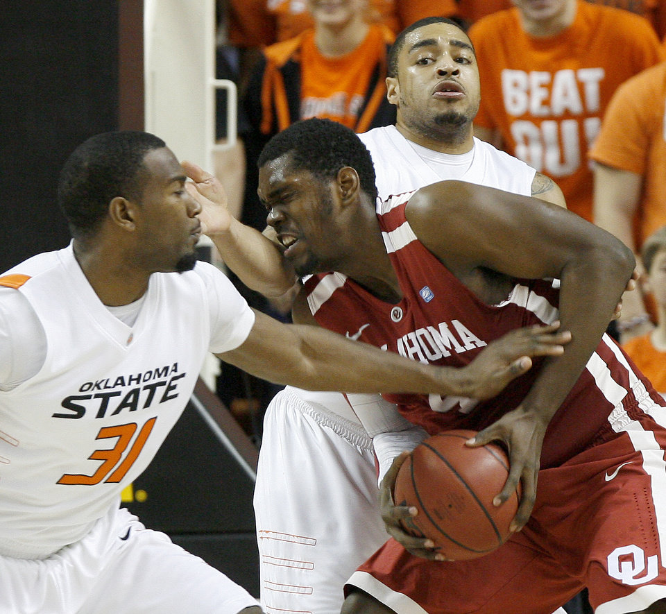 Photo - Oklahoma's Andrew Fitzgerald (4) tries to get past Oklahoma State's Matt Pilgrim (31) and Marshall Moses (33) during the Bedlam men's college basketball game between the University of Oklahoma Sooners and Oklahoma State University Cowboys at Gallagher-Iba Arena in Stillwater, Okla., Saturday, February, 5, 2011. Photo by Bryan Terry, The Oklahoman