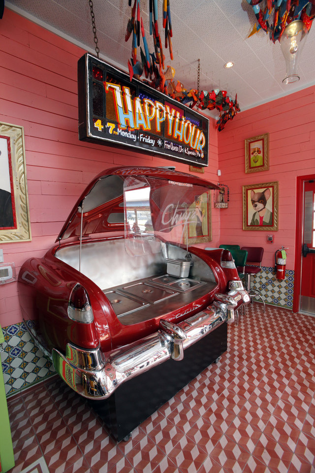 Photo - Decorations at the bar at the new Chuy's restaurant  in Norman include half a car.  STEVE SISNEY - THE OKLAHOMAN
