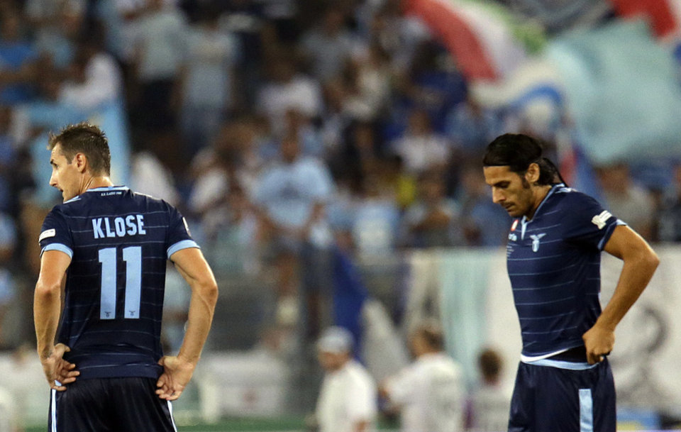 Lazio forward Miroslav Klose, of Germany, left, and his teammate Sergio Floccari, stand on the pitch after Juventus' Carlos Tevez scored during their Italian Supercup soccer match at the Rome Olympic stadium Sunday, Aug. 18, 2013. (AP Photo/Gregorio Borgia)