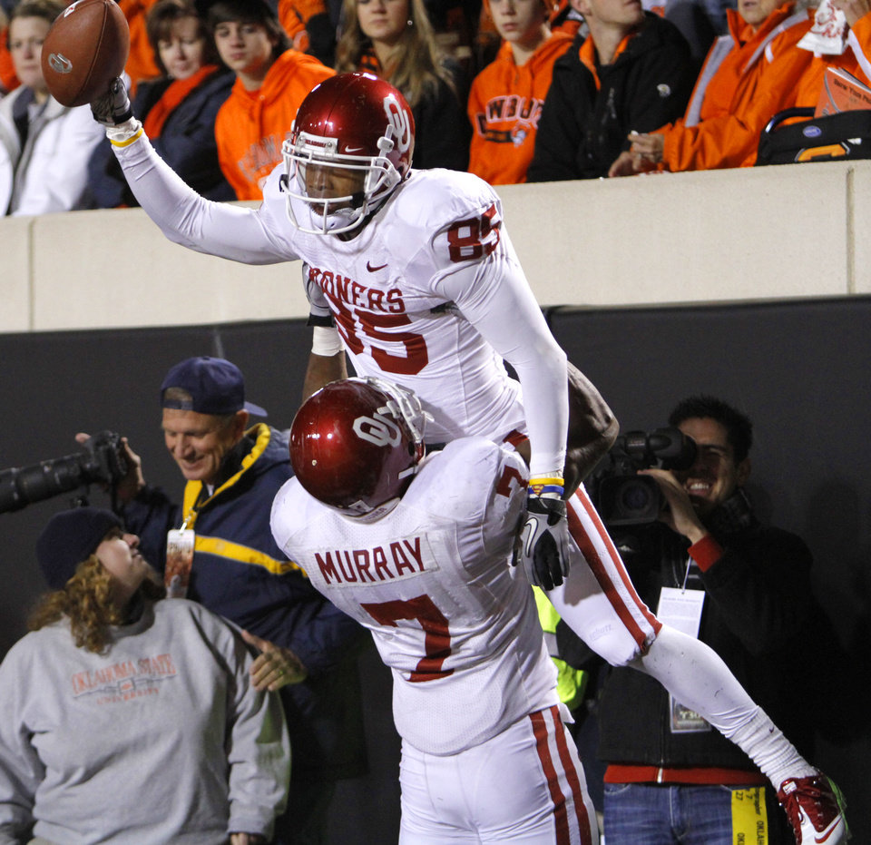 Photo - CELEBRATION: Oklahoma's DeMarco Murray (7) lifts Ryan Broyles (85) as they celebrate Broyles' touchdown during the Bedlam college football game between the University of Oklahoma Sooners (OU) and the Oklahoma State University Cowboys (OSU) at Boone Pickens Stadium in Stillwater, Okla., Saturday, Nov. 27, 2010. Photo by Chris Landsberger, The Oklahoman ORG XMIT: KOD