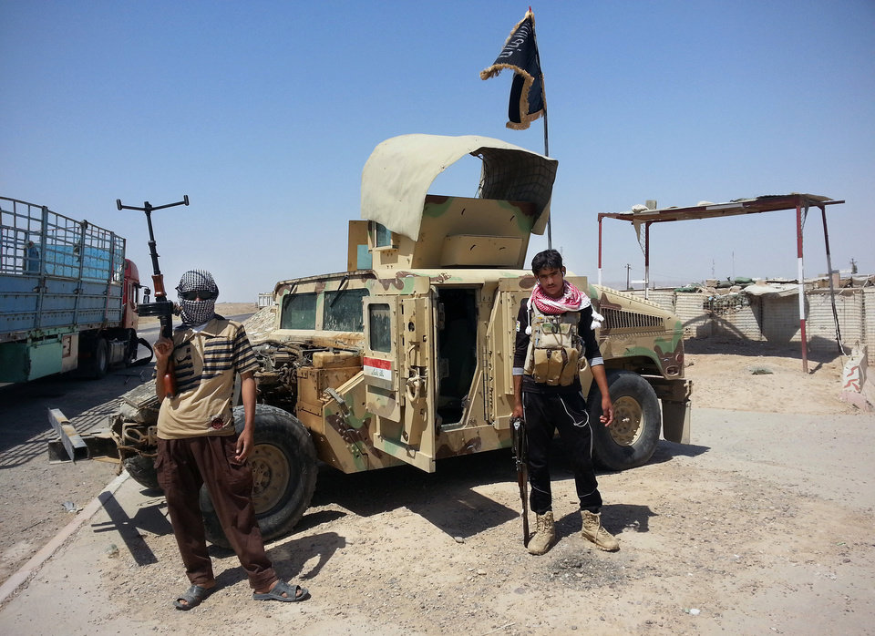 Photo - Al-Qaeda inspired militants stand with captured Iraqi Army Humvee at a checkpoint outside Beiji refinery, some 250 kilometers (155 miles) north of Baghdad, Iraq, Thursday, June 19, 2014. The fighting at Beiji comes as Iraq has asked the U.S. for airstrikes targeting the militants from the Islamic State of Iraq and the Levant. While U.S. President Barack Obama has not fully ruled out the possibility of launching airstrikes, such action is not imminent in part because intelligence agencies have been unable to identify clear targets on the ground, officials said.(AP Photo)