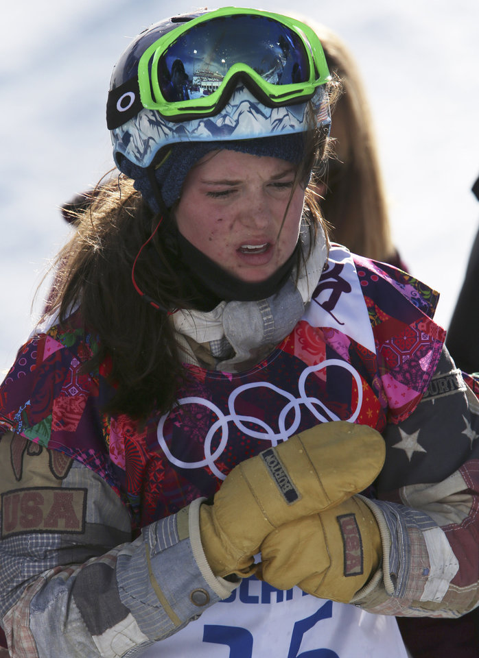 Photo - United States' Arielle Gold walks off the course after injuring her hand in a crash during the women's snowboard halfpipe qualifying at the Rosa Khutor Extreme Park, at the 2014 Winter Olympics, Wednesday, Feb. 12, 2014, in Krasnaya Polyana, Russia. (AP Photo/Sergei Grits)