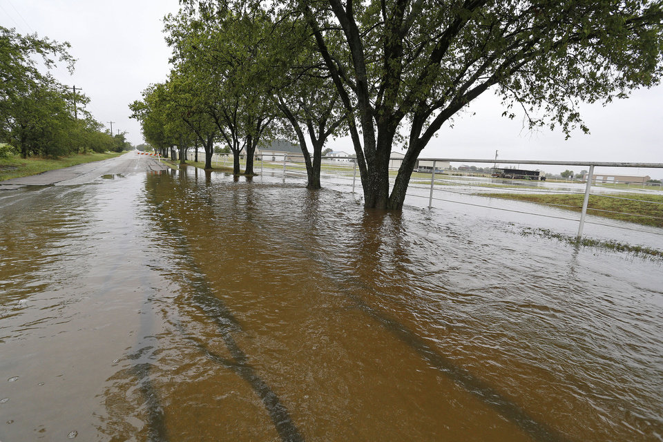 Photo - Floodwaters cover the road near the intersection of Hopkins and Radecke Roads in Krum, Texas on Thursday, July 17, 2014 after heavy rains in the area. (AP Photo/Fort Worth Star-Telegram, Paul Moseley)