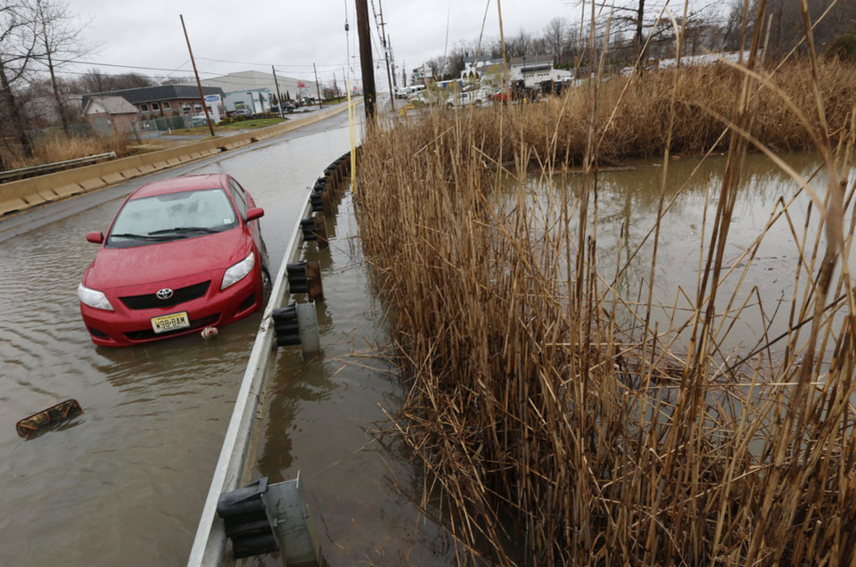 Photo - A vehicle stands abandoned facing in the wrong direction with floodwaters surrounding it on Route 35 in Keyport, N.J., where an overnight storm caused coastal flooding, Thursday, Dec. 27, 2012. (AP Photo/Julio Cortez)