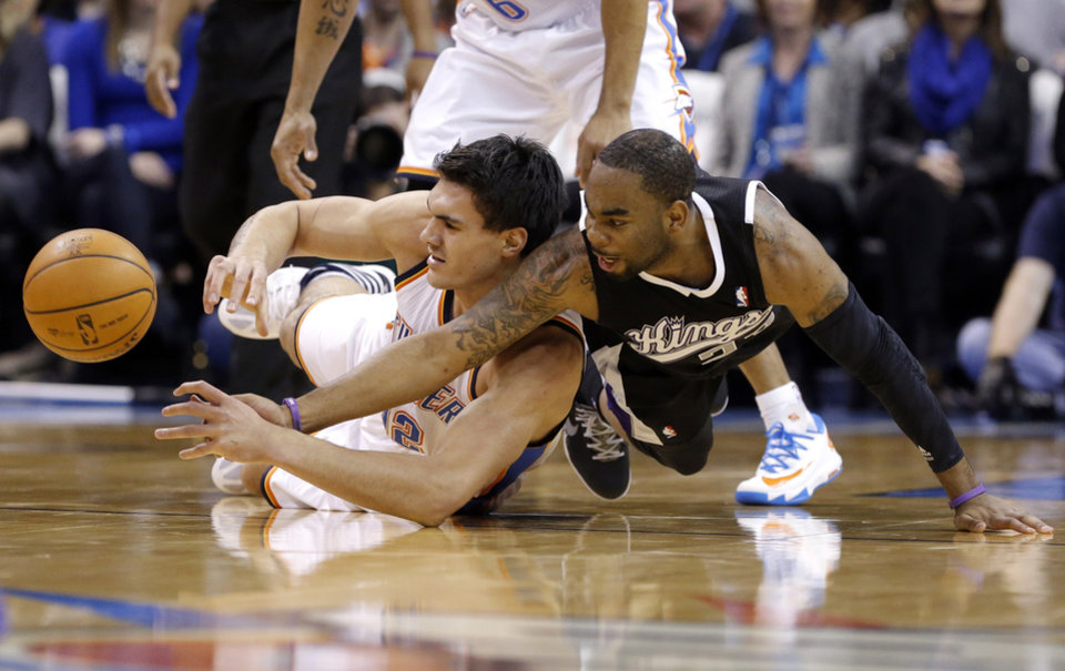 Photo - Oklahoma City's Steven Adams (12) and Sacramento's Marcus Thornton (23) fight for a loose ball during the NBA game between the Oklahoma City Thunder and the Sacramento Kings at the Chesapeake Energy Arena, Sunday, Jan. 19, 2014.  Photo by Sarah Phipps, The Oklahoman