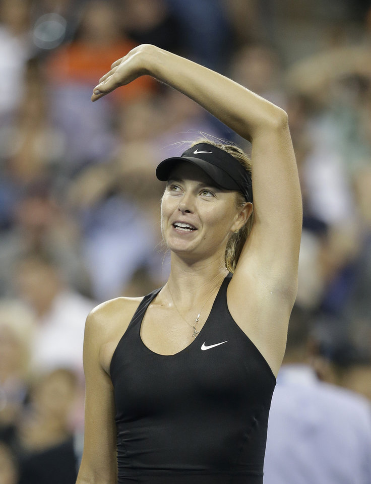Photo - Maria Sharapova, of Russia, waves to fans after defeating Maria Kirilenko, of Russia, 6-4, 6-0 during the opening round of the U.S. Open tennis tournament Monday, Aug. 25, 2014, in New York. (AP Photo/Darron Cummings)