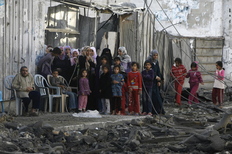 Palestinians stand near the rubble of the building of Attia Abu Inkara, a Hamas militant leader, following an Israeli air strike in Rafah refugee camp in southern Gaza Strip, Sunday, Nov. 18, 2012. An Israeli envoy held talks with Egyptian officials Sunday on a ceasefire in his country\'s offensive on Gaza as Israel widened the range of its targets, striking more than a dozen homes of Hamas militants and two media officials. (AP Photo/Eyad Baba)