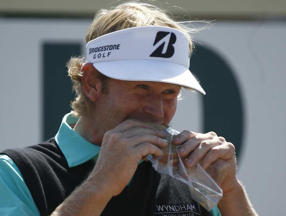Brandt Snedeker of the United States eats a sandwich on the 10th hole during the third round of the British Open Golf Championship at Muirfield, Scotland, Saturday July 20, 2013. (AP Photo/Jon Super)