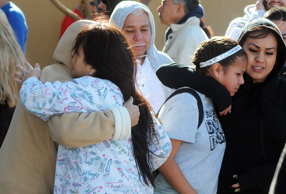 Photo - Students are reunited with families at a staging ground area set up at the Roswell Mall following a shooting at Berrendo Middle School, Tuesday, Jan. 14, 2014, in Roswell, N.M. A shooter opened fire at the middle school, injuring at least two students before being taken into custody. Roswell police said the school was placed on lockdown, and the suspected shooter was arrested. (AP Photo/Roswell Daily Record, Mark Wilson)