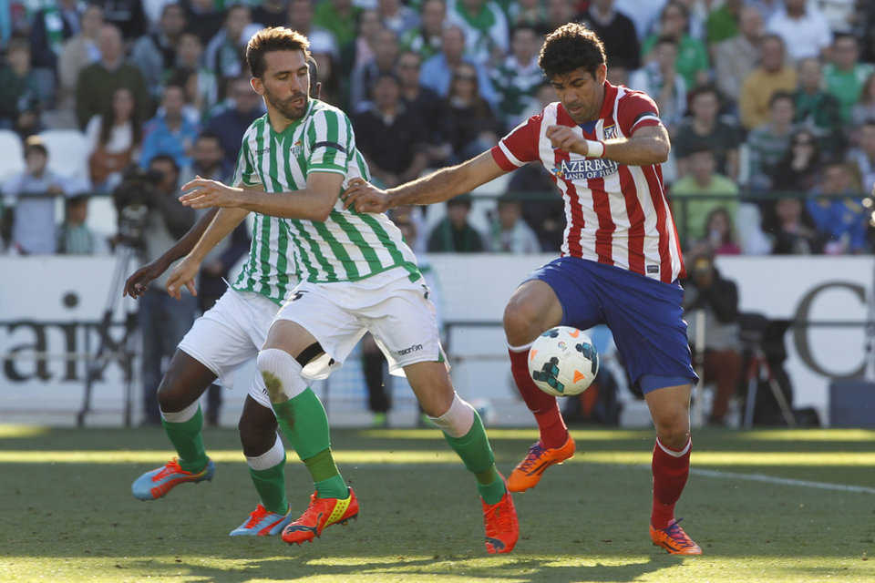 Photo - Atletico de Madrid's Diego Costa, right, and Betis'  Jordi Figueras , left, vie for the ball during their La Liga soccer match at the Benito Villamarin stadium, in Seville, Spain on Sunday, March 23, 2014. (AP Photo/Angel Fernandez)