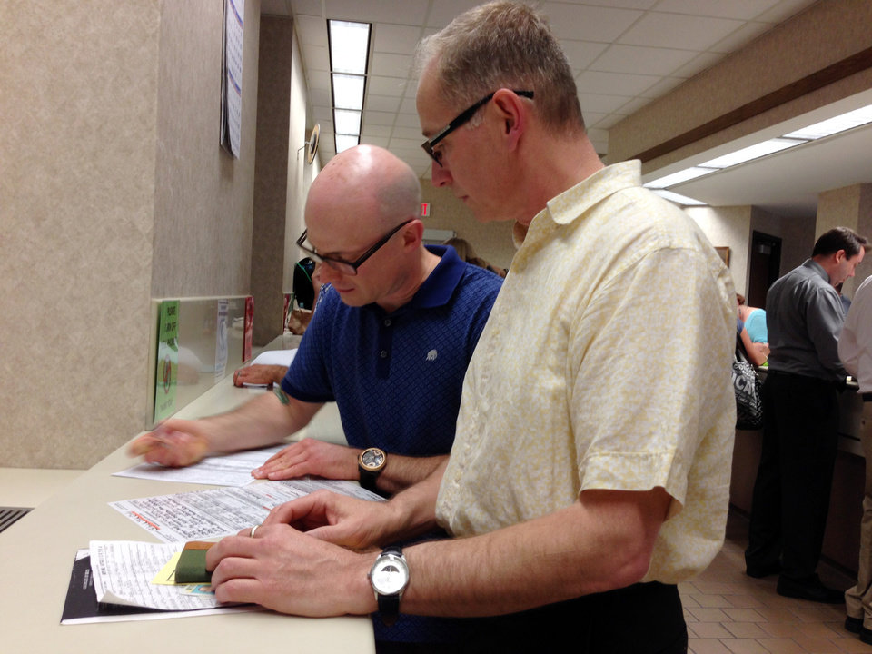 Photo - Mark Williams, left, and Chrisopher Martell, right, fill out an application for a marriage license at the Milwaukee County Clerk's office Friday, June 6, 2014, in Milwaukee. Same-sex couples began getting married in Wisconsin on Friday shortly after a federal judge struck down the state's gay marriage ban and despite confusion over the effect of the ruling. (AP Photo/M.L.Johnson)
